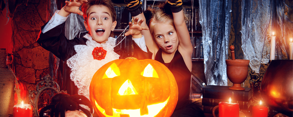 two kids and a carved pumpkin for a Halloween concept