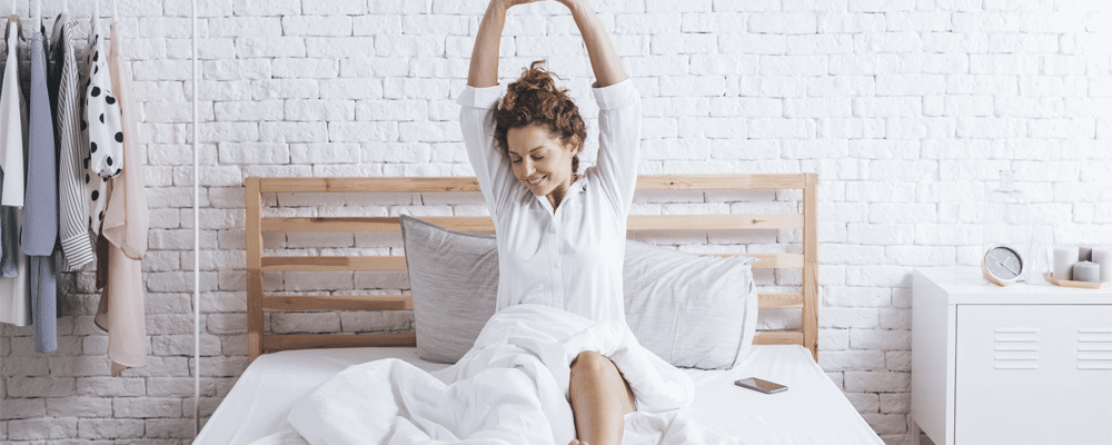 a woman stretching after waking up happily on a memory foam mattress