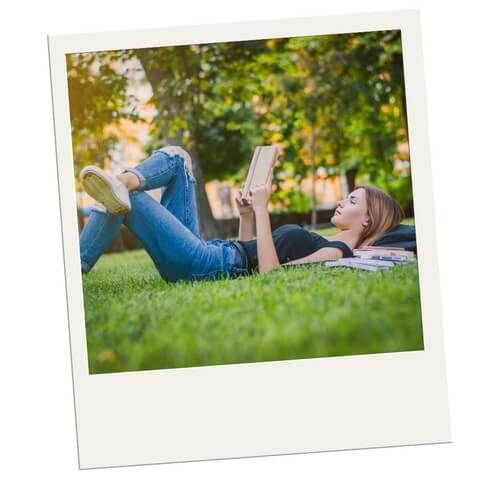 College Thanksgiving Break a Girl laying in the Grass Reading