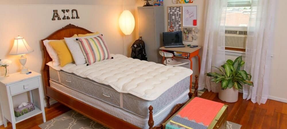 a dormtopper on a mattress inside a decorated bedroom